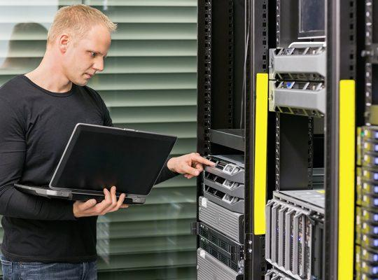 It engineer or consultant standing with a laptop and monitor blade servers in data rack. Shot in datacenter.