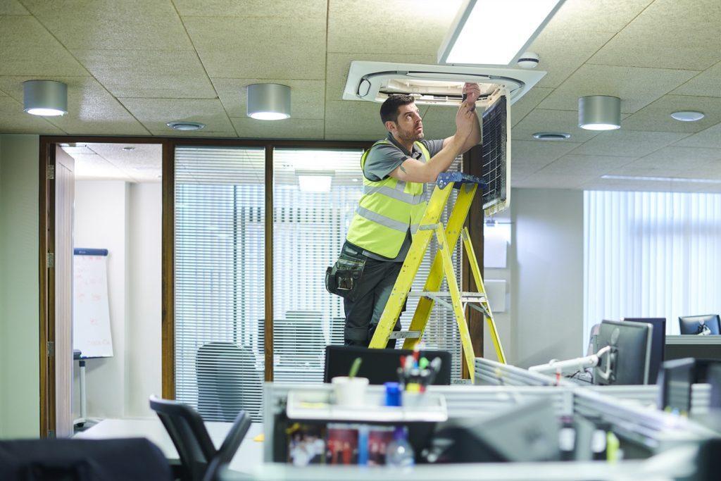 mężczyzna sprawdza klimatyzacje w biurze